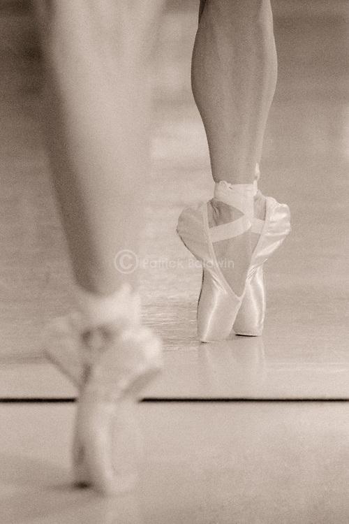 A dancer en pointe reflected in a mirror.
