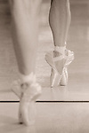 A dancer en pointe reflected in a mirror.