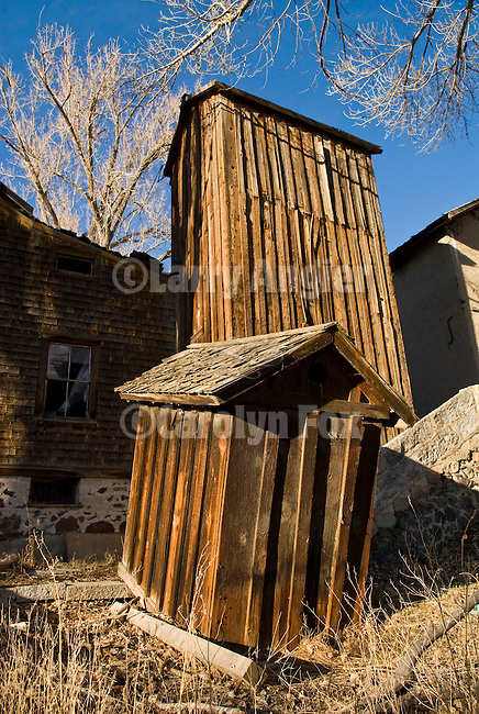 Collapsing and leaning outhouse by the creek, winter..Leaning, enclosed wooden water tank tower