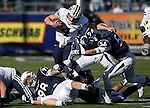 BYU quarterback Taysom Hill (4) runs up the middle against Nevada defenders Jack Reynoso (98), left, Lenny Jones, (94) and Alex Bertrando, (56) in an NCAA college football game in Reno, Nev., on Saturday, Nov. 30, 2013. BYU defeated Nevada 28-23. (AP Photo/Cathleen Allison)