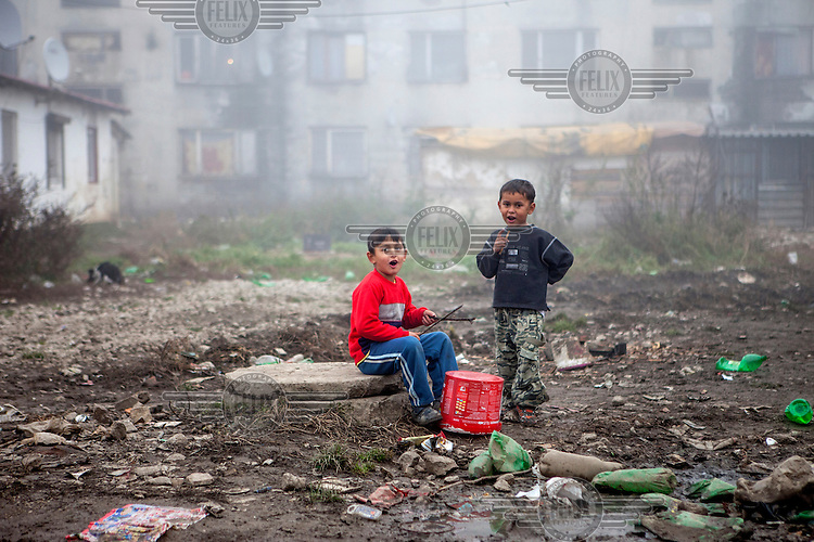 Two boys using a bucket as a drum on a patch of ground in the Roma settlement located in 'Budulovskej Street'.