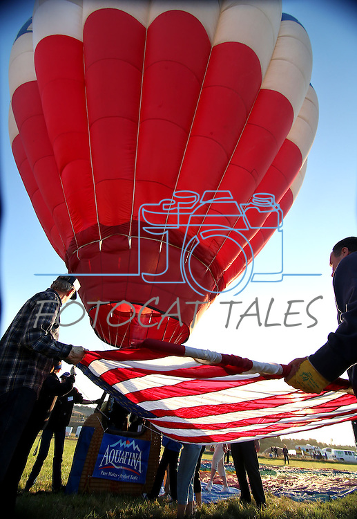 Crew members attach the American flag to a balloon at the start of media day at the 32nd annual Great Reno Balloon Race in Reno, Nev., on Thursday, Sept. 5, 2013.  <br /> Photo by Cathleen Allison