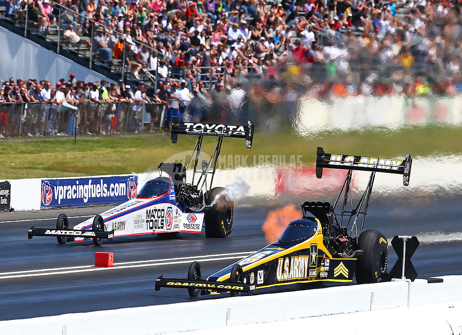 Jun. 1, 2014; Englishtown, NJ, USA; NHRA top fuel driver Tony Schumacher (near) races alongside Antron Brown during the Summernationals at Raceway Park. Mandatory Credit: Mark J. Rebilas-