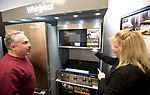 WATERBURY , CT-011519JS03- Owners John and Pam Ciccio, demonstrates the features on a Whirlpool smart range and microwave on display at Allstar Appliance in Waterbury on Tuesday. <br /> Jim Shannon Republican American