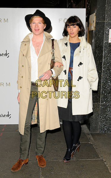 HENRY CONWAY & GUEST.The Form menswear launch, Harrods, Knightsbridge, London, England..October 2nd, 2008.full length beige mac trenchcoat black hat white shirt unbuttoned grey gray trousers tights arms linked .CAP/CAN.©Can Nguyen/Capital Pictures.