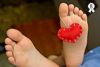 Valentine heart hanging on girl's (6-7) barefeet (Licence this image exclusively with Getty: http://www.gettyimages.com/detail/sb10066226k-001 )