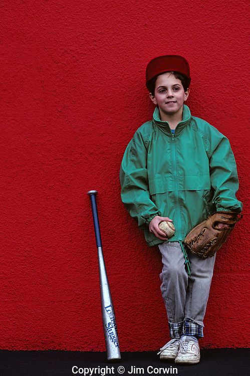 Young boy standing in front of red wall getting his portait taken holding a baseball and mitt Seattle Washington State USA