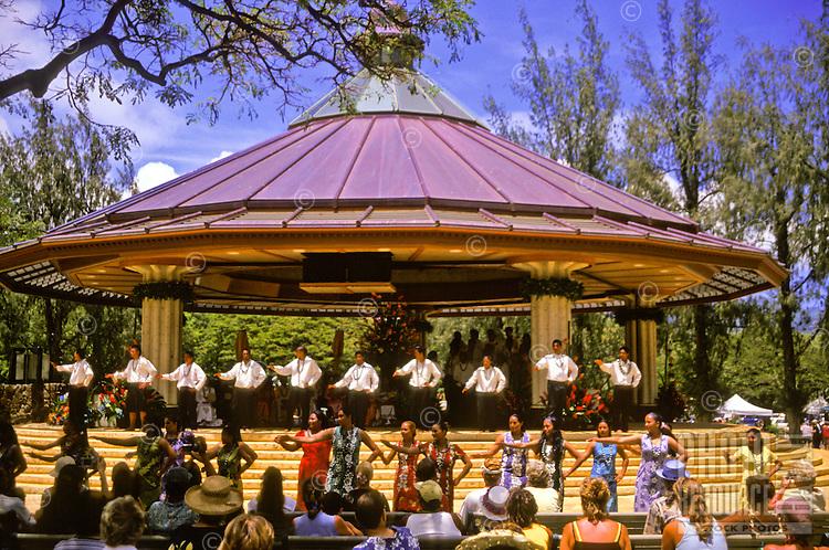 A hula halau (school or group) performs at the Kapiolani Park Bandstand in Waikiki