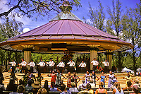 A hula halau (school or group) performs at the Kapiolani Park Bandstand in Waikiki