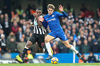 Chancel Mbemba of Newcastle United and Marcos Alonso of Chelsea battle for the ball during the Premier League match between Chelsea and Newcastle United at Stamford Bridge, London, England on 2 December 2017. Photo by David Horn.