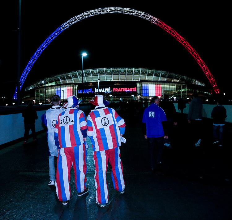 Fans with pictures commemorating the Paris terrorist attacks arrive at an illuminated Wembley Stadium, home of England football<br /> <br /> Photographer Craig Mercer/CameraSport<br /> <br /> Football International - England v France - Tuesday 17th November 2015 - Wembley Stadium - London<br /> <br /> &copy; CameraSport - 43 Linden Ave. Countesthorpe. Leicester. England. LE8 5PG - Tel: +44 (0) 116 277 4147 - admin@camerasport.com - www.camerasport.com