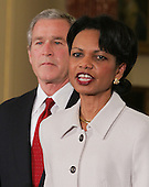 US President George W. Bush listens as  Secretary of State Condoleezza Rice delivers remarks during a swearing in ceremony in the Benjamin Franklin Room of the Department of State in Washington, DC Friday 28 January 2005. Secretary Rice, who is the second woman and the first black woman to become Secretary of State, was sworn in by White House chief of staff Andrew Card Wednesday evening, hours after the Senate confirmed her by a vote of 85 to 13,  in a private ceremony at the White House.<br /> Credit: Shawn Thew / Pool via CNP