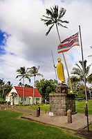The original King Kamehameha I Statue and Hawaiian State Flag, with the Bond Memorial Public Library in background. Kapa'au, Big Island, Hawaii