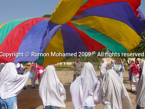 Ramon Mohamed, from Sheffield, UK, organises games with a parachute he brought with him,  Matayal Girls School, Kotli area, Azad Kashmir, Pakistan.  Built with donations from the UK Kashmiri community.