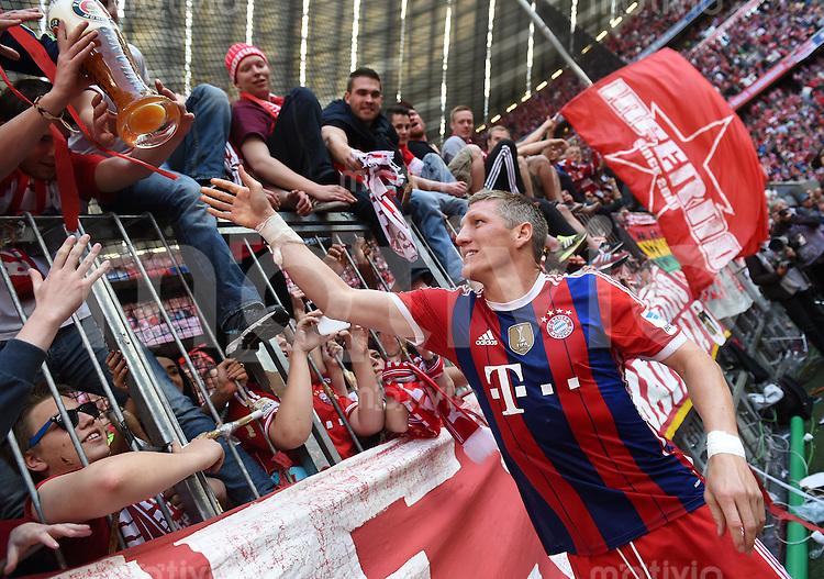 FUSSBALL   1. BUNDESLIGA   SAISON 2013/2014  34. SPIELTAG FC Bayern Muenchen - VfB Stuttgart             10.05.2014 Der FC Bayern feiert die 24. Deutsche Meisterschaft: Bastian Schweinsteiger verteilt Weissbier an die Fans in der Suedkurve in der Allianz Arena