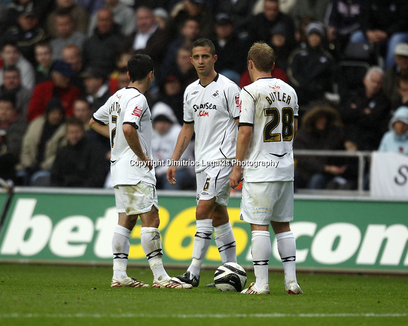 Pictured: (L-R) Leon Britton, Ferrie Bodde and Thomas Butler of Swansea City in action <br />