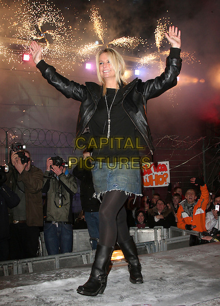 ULRIKA JONSON .during the final of Celebrity Big Brother 2009 at Elstree Studios, Borehamwood, Herts, England, January 23rd 2009. .full length black leather jacket silver tassel necklace winner top Johnson Jonsson Jonnson denim skirt tights  hands fireworks ankle biker boots  waving .CAP/ROS.©Steve Ross/Capital Pictures