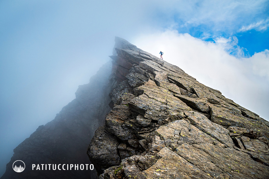 A trail runner running up a steep rocky ridge line in thick cloud, above Saas Almagell, Switzerland.