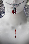Close-up of pale female mouth and neck with necklace and drop of blood