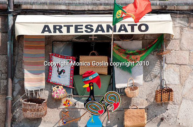 Typical crafts of Portugal on display outside a tourist shop in Porto, Portugal. Crafts of Portugal including straw baskets, the wooden rooster, and a child's toy.