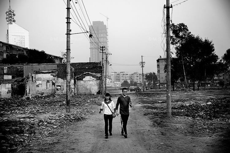A couple walks past destroyed hutongs, or traditional Chinese residential alleys, in central Tianjin, China, which have been demolished to make room for modern high-rise building construction.