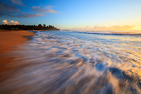 Ocean surf rushes onto shore with the warm light of early morning at Kealia Beach, Kapa'a, Kaua'i.