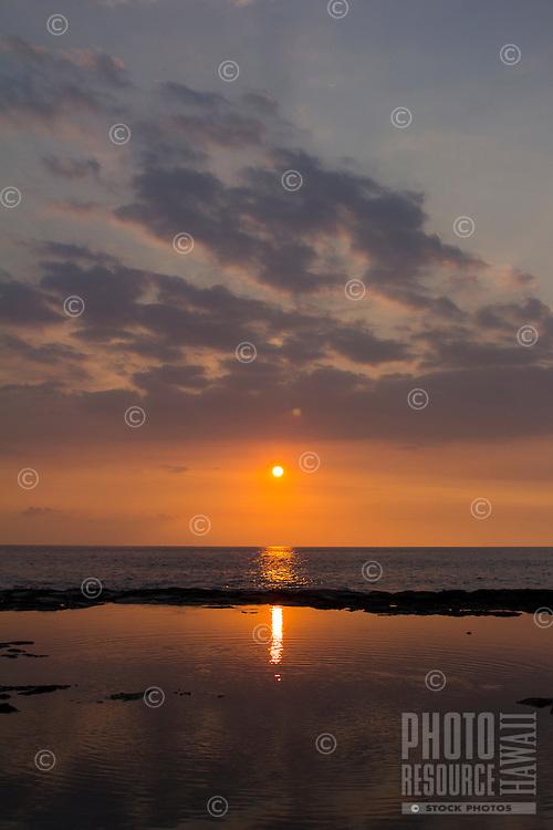 Colorful Kona sunset reflected in a tide pool, Big Island.