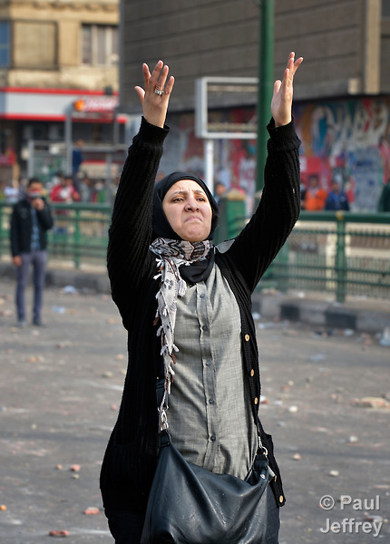 A woman defiantly gestures toward police during November 25, 2012, protests in and around Cairo's Tahrir Square. The demonstrators were upset by Egyptian President Mohammed Mursi's November 22nd decision to assume sweeping new powers.