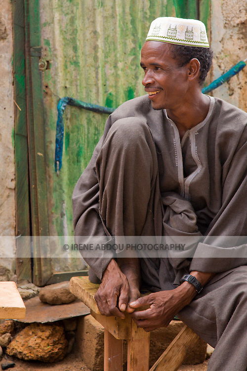 Siddal Dicko sits on a wood bench in Ouagadougou, Burkina Faso.  Siddal is Fulani from the Djibo region of eastern Burkina Faso.  He has come to the capital to visit relatives.