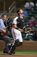 Salt River Rafters catcher Oscar Hernandez (25) tracks a foul ball popup in front of umpire Carlos Torres during an Arizona Fall League game against the Scottsdale Scorpions on October 13, 2015 at Salt River Fields at Talking Stick in Scottsdale, Arizona.  Salt River defeated Scottsdale 5-3.  (Mike Janes/Four Seam Images)