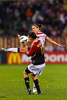 Lauren Cheney (12) of the United States (USA) passes the ball under pressure from Viola Odebrecht (17) of Germany (GER). The United States (USA) and Germany (GER) played to a 2-2 tie during an international friendly at Rentschler Field in East Hartford, CT, on October 23, 2012.