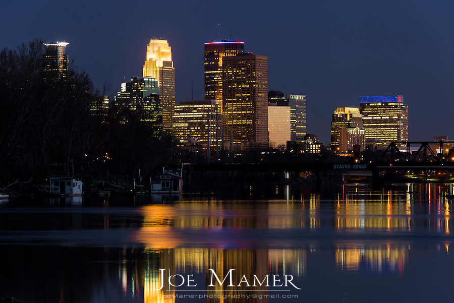 Minneapolis skyline reflected in the Mississippi River at dusk.
