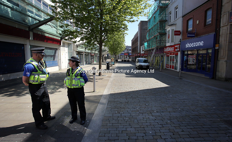 Pictured: Police at the junction of Union and Oxford Street in Swansea city centre with the entrance to the Quadrant in the background Wednesday 24 May 2017<br />