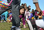Aylaina  Ogawa, 6, of Avon, grabs a plastic egg while looking for the next one,  during the 41st Annual Imperial Oil Egg Hunt,  Friday, April 6, 2012, at South Windsor High School. (Jim Michaud/Journal Inquirer)..