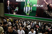Subway crowds walk underneath a Tsingtao Beer billboard in the Shanghai Metro in Shanghai, China.