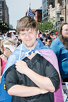 A man wears a Straight Pride flag like a cape and holds an American flag in the Straight Pride Parade in Boston, Massachusetts, on Sat., August 31, 2019.