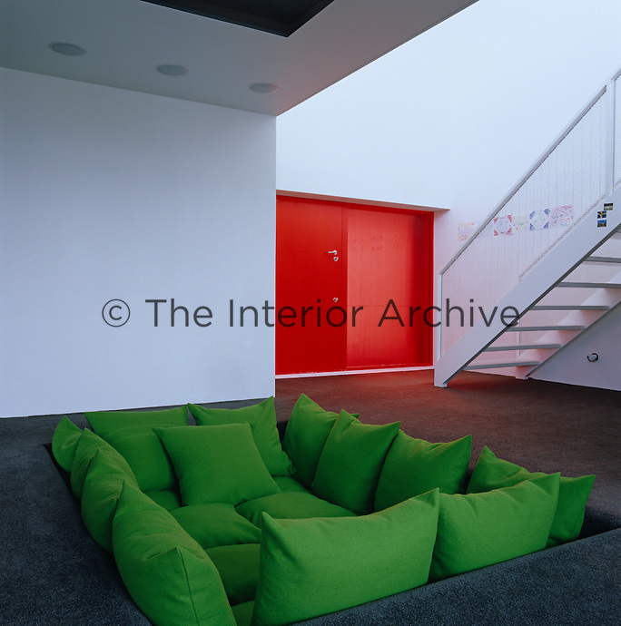 "A 'conversation pit"" on the lower level is filled with green cushions and is the ideal place from which to watch television"