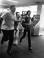 Michael Jackson with body guards runs thru the Oakland Airport concourse after landing. (1981 photo/Ron Riesterer)