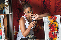 Texting and selling her art at the market, La Habana Vieja