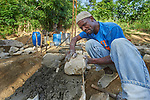 Saintorick Joseph places stones in the foundation of a house being built by Church World Service for a family that lost their home in Lareserve, a village near Jean-Rabel in northwestern Haiti, during Hurricane Matthew in 2016.  <br /> <br /> CWS is a member of the ACT Alliance.