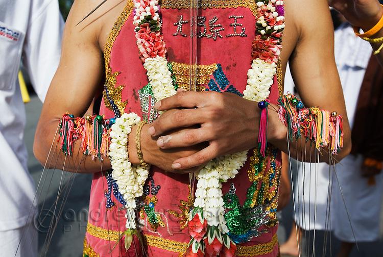 A Ma-Thong (spirit medium) with his arms pierced with metal skewers during the Phuket Vegetarian Festival.  Phuket, Ko Phuket, THAILAND.