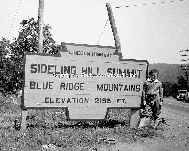 Harrisonville PA:  View of Brady Stewart Jr. standing next to the famous Sideling Hill Summit sign on Route 30 in Fulton County - 1931.