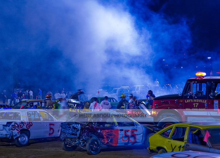 At the demolition derby in Gaithersburg, Maryland, a car flips over, creating sheaths of billowing blue smoke, as a fire truck races to the rescue. The driver emerges unscathed to the cheering screams of the crowd.  The demolition derby is one of many events at the annual Montgomery County Agricultural Fair in Gaithersburg, Maryland.