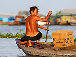 MAN ON BOAT IN CHONG KOS FLOATING VILLAGES AT TONLE SAP RIVER