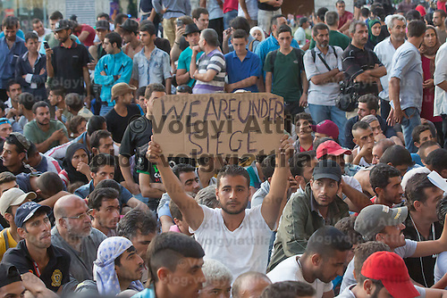Illegal migrant holds a banner during a protest against their denial to travel to Germany at the main railway station Keleti in Budapest, Hungary on September 02, 2015. ATTILA VOLGYI