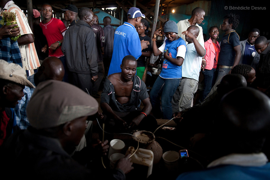 Kenyans dance and drink Busaa, a traditional fermented beer, in a crowded Busaa club at midday in a Nairobi slum on April 7, 2013. Busaa is made by crudely fermenting maize, millet, sorghum or molasses. At Kshs 35 per liter it is much cheaper than a Kshs120 half-liter bottle of commercial beer. The local brew was legalised in 2010 and since then Busaa clubs have become increasingly popular in slums and rural areas. Drinking is on the rise in Kenya, especially among young people. Photo by Benedicte Desrus