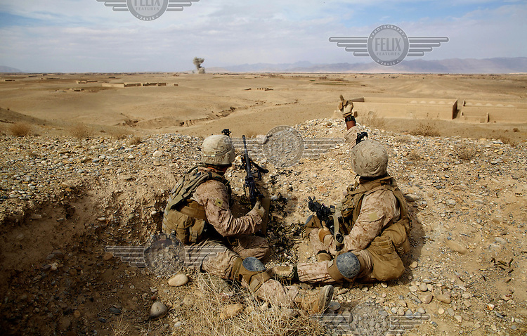 Soldiers from 3rd Marines/5th Infantry watch a Himar GPS guided missile strike on a compound during a prolonged gunfight with insurgents near the Kajaki Dam.