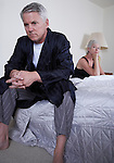 Mature couple sitting apart on bed