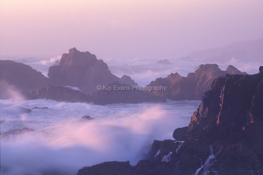 Waves crash along the coast of Big Sur at sunset.