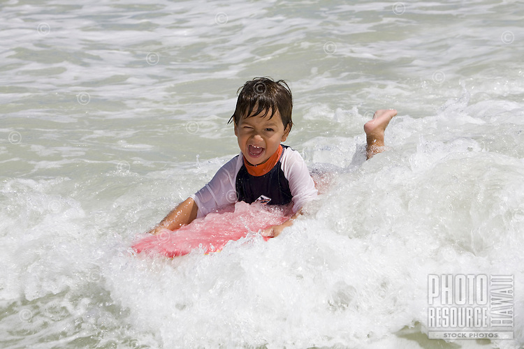 A small boy rides a wave using a body board at Kailua Beach, Oahu, Hawaii.